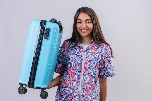 Młoda piękna podróżniczka kobieta trzyma walizkę patrząc pewnie pozytywnie i szczęśliwie uśmiechając się wesoło gotowa do podróży stojąc na białym tle