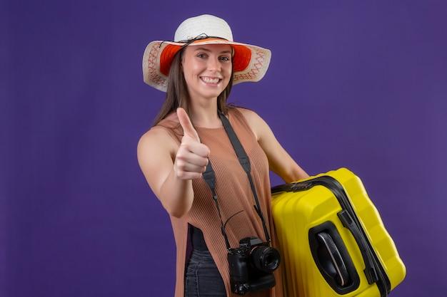 Młoda piękna podróżniczka kobieta w kapeluszu lato z żółtą walizką i aparatem fotograficznym, uśmiechając się radośnie, pokazując kciuki do góry