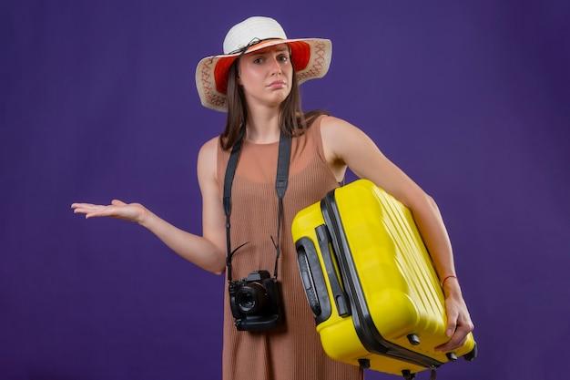 Młoda piękna podróżniczka kobieta w kapeluszu lato z żółtą walizką i aparatem patrząc zdezorientowana, nie mając odpowiedzi stojącej na fioletowym tle