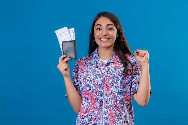 Młoda piękna podróżniczka trzyma paszport z biletami patrząc w kamerę, uśmiechając się wesoło, podnosząc pięść po zwycięstwie gotowa do wakacji, stojąc na odosobnionym niebieskim tle