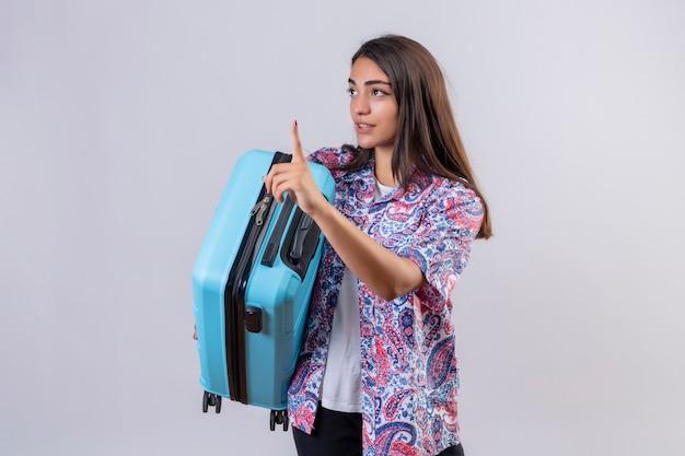 Młoda piękna podróżniczka trzyma walizkę gestykulując poczekaj minutę z poważnym pewnym wyrazem twarzy stojącej na białym tle