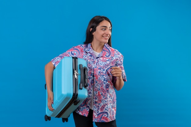 Młoda piękna podróżniczka trzyma walizkę pewnie, pozytywnie i szczęśliwie, uśmiechnięta wesoło, gotowa do podróży po niebieskiej ścianie