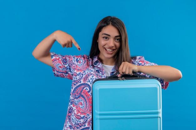 Młoda piękna podróżniczka trzyma walizkę wskazując palcem wskazującym na nią, wyglądająca na pewną siebie pozytywną i szczęśliwą, uśmiechniętą wesoło gotową do podróży stojącą na niebieskim tle