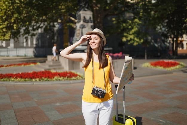 Młoda piękna podróżniczka turystyczna kobieta w kapeluszu z walizką, mapa miasta retro vintage zdjęcie aparat spaceru w mieście na świeżym powietrzu. dziewczyna wyjeżdża za granicę na weekendowy wypad. styl życia podróży turystycznej.