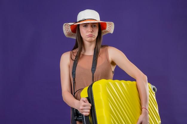 Młoda piękna podróżniczka w letnim kapeluszu z żółtą walizką i aparatem fotograficznym niezadowolona, dmuchająca w policzki z nieszczęśliwą twarzą na fioletowej ścianie