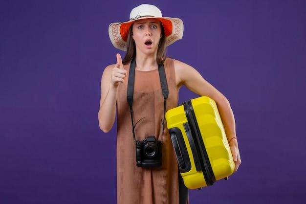 Młoda piękna podróżniczka w letnim kapeluszu z żółtą walizką i aparatem fotograficznym wskazująca palcem na aparat zaskoczona i zdumiona stojąca na fioletowym tle