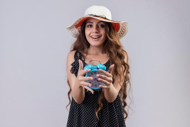 Młoda piękna podróżniczka w sukience w groszki w letnim kapeluszu trzyma budzik patrząc na kamerę, uśmiechając się radośnie ze szczęśliwą twarzą stojącą na białym tle