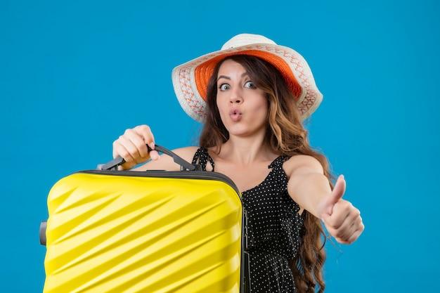 Młoda piękna podróżniczka w sukience w groszki w letnim kapeluszu trzyma walizkę wyglądająca na podekscytowaną i szczęśliwą pokazującą kciuki do góry, ciesząc się jej sukcesem i zwycięstwem stojącym na niebieskim tle