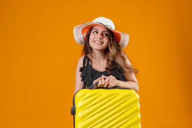 Młoda piękna podróżniczka w sukience w groszki w letnim kapeluszu trzymająca walizkę patrząc na bok uśmiechnięta wesoło szczęśliwa i pozytywna pozycja na pomarańczowym tle