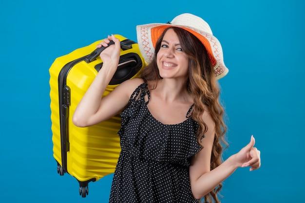 Młoda piękna podróżniczka w sukience w groszki w letnim kapeluszu trzymająca walizkę patrząc na bok uśmiechnięta wesoło szczęśliwa i pozytywnie pokazująca kciuki stojąc na niebieskim tle