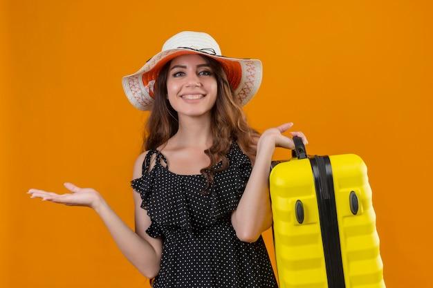Młoda piękna podróżniczka w sukience w groszki w letnim kapeluszu trzymająca walizkę patrząc na kamery z radosną twarzą uśmiechniętą wesoło, przedstawiającą ręką stojącą nad żółtym backgrou