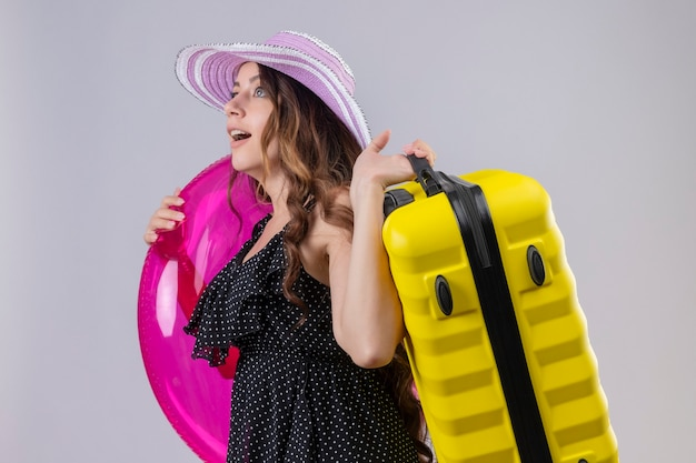 Młoda piękna podróżniczka w sukience w kropki w letnim kapeluszu trzyma nadmuchiwany pierścionek i walizkę odwracając wzrok zaskoczony i zdumiony stojąc na białym tle
