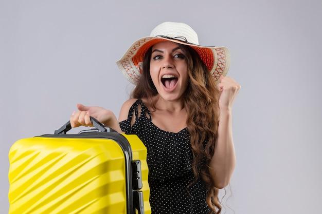 Młoda piękna podróżniczka w sukience w kropki w letnim kapeluszu trzyma walizkę, patrząc podekscytowany i szczęśliwy podnosząc pięść, ciesząc się jej sukcesem i zwycięstwem stojącym na białym tle