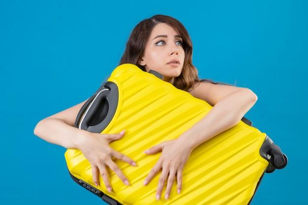 Młoda piękna podróżnik dziewczyna trzyma walizkę nerwowy i bardzo niespokojny, patrząc od stojącego na niebieskim tle