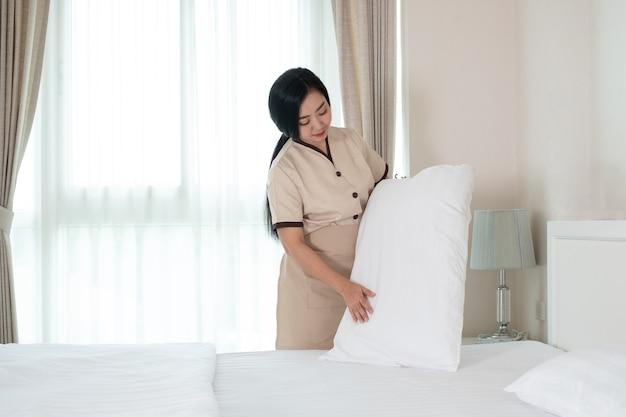 Młoda piękna pokojówka z azji układa poduszkę na łóżku w pokoju hotelowym