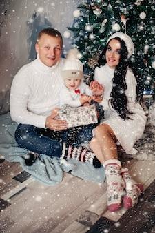 Młoda piękna rodzina z dzieckiem w świątecznej atmosferze uśmiecha się razem