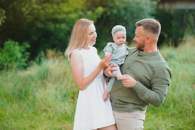 Młoda piękna rodzina z małą córeczką przytulić, pocałować i chodzić w przyrodzie o zachodzie słońca. zdjęcie rodziny z małym dzieckiem na łonie natury.