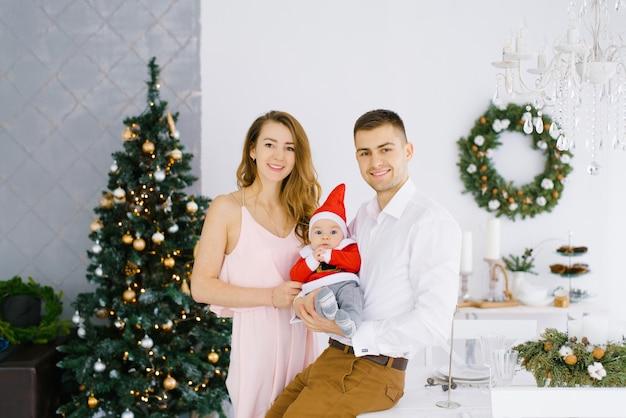 Młoda piękna rodzina z pięciomiesięcznym dzieckiem w małym stroju świętego mikołaja w ramionach rodziców.
