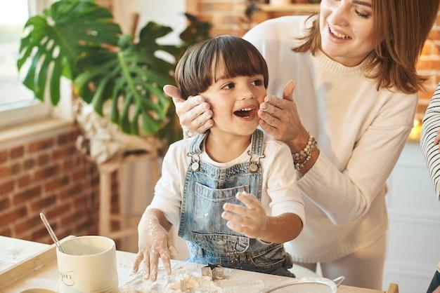 Młoda piękna rodzina zabawy i gotowania w słonecznej kuchni