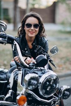 Młoda piękna rowerzysta dziewczyna w okularach i skórzanej kurtce na motocyklu. pojęcie prędkości i wolności