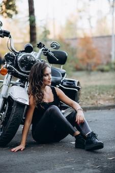 Młoda piękna rowerzystka w czarnym podkoszulku i skórzanych spodniach siedzi na chodniku w pobliżu motocykla. pojęcie prędkości i wolności