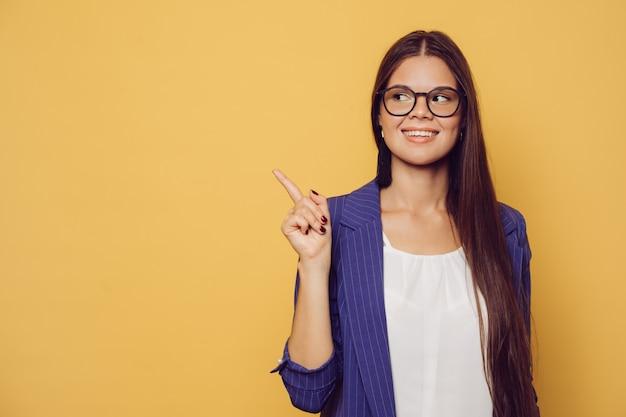 Młoda piękna rozochocona dziewczyna w zmroku - błękitna kurtka nad żółtym tłem uśmiechniętym i patrzeje kamerę wskazuje strona przy kopii przestrzenią.