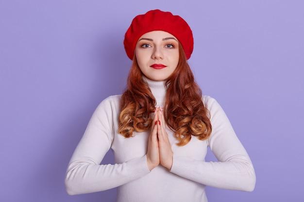 Młoda piękna ruda kobieta ubrana w czerwony francuski beret i białą koszulę na bzu przestrzeni