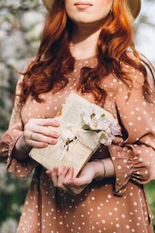 Młoda piękna rudowłosa dziewczyna spacery w kwitnącym wiosną sadzie jabłkowym