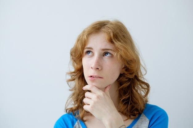 Młoda piękna rudowłosa europejka z wyrazem wątpliwości i niezadowoleniem na zmartwionej twarzy