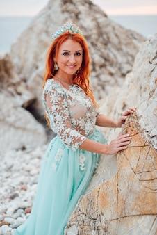 Młoda piękna rudowłosa kobieta w luksusowej sukience stoi na skalistym brzegu adriatyku wśród dużych kamieni, zbliżenie