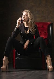 Młoda piękna seksowna blondynka w czarnej kurtce i bieliźnie ze szklaną whisky na ciemnym tle