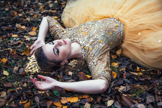 Młoda piękna seksowna dziewczyna w złotej sukni w jesień lesie