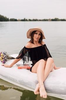 Młoda piękna seksowna kobieta pływa na materacu wodnym