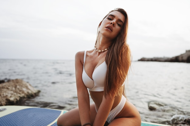 Młoda piękna seksowna kobieta pozuje w morzu na desce sup