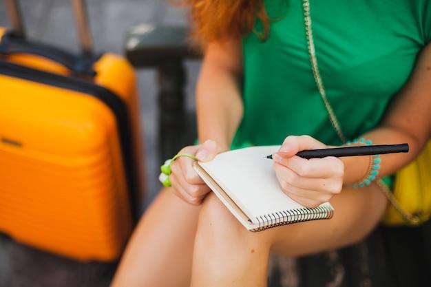 Młoda piękna seksowna kobieta, strój hipster, podróżnik, pomarańczowa walizka, robienie notatek w dzienniku podróży, wakacje, przygoda, podróż, kolorowe, ręce pisanie, długopis, szczegóły z bliska