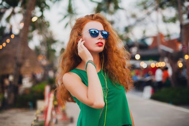 Młoda piękna seksowna kobieta, styl hipster, rude włosy, podróżnik, zielony top, pomarańczowa walizka, wakacje, podróże, okulary przeciwsłoneczne, słuchanie muzyki, słuchawki, okulary przeciwsłoneczne, tropikalna wycieczka