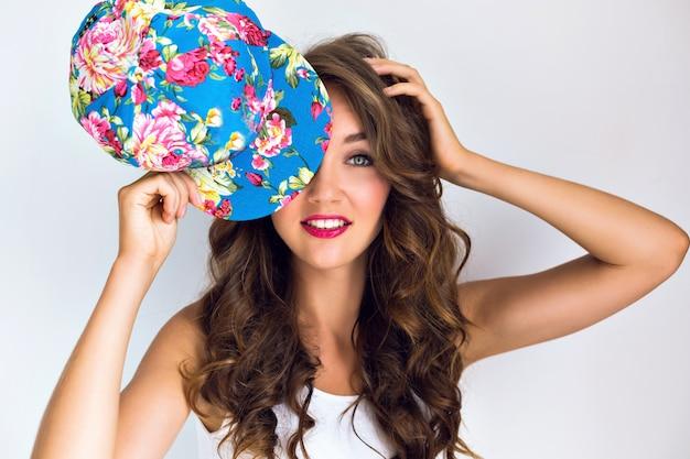 Młoda piękna seksowna kobieta zamknęła oczy kwiatowy czapkę. jasny makijaż z czerwonymi ustami i długimi kręconymi włosami. zaskoczone emocje.