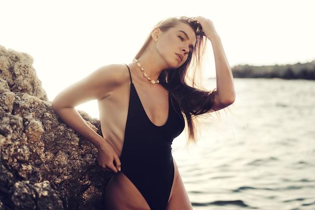 Młoda piękna seksowna modelka w czarnym bikini stojąca w morzu w pobliżu ogromnej skały