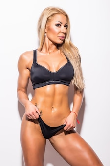 Młoda piękna seksowna muskularna młoda kobieta w kostiumie kąpielowym. bikini fitness. muskularne, szczupłe ciało. na białym tle
