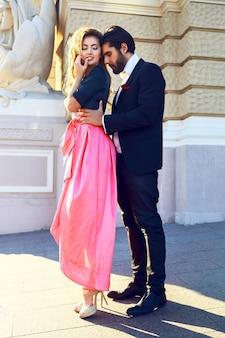 Młoda piękna seksowna para przytula się na ulicy, cieszy się romantyczną randką, spędza miło czas, pozując na ulicy w klasycznych modnych wieczorowych ciuchach glamour. jasne, słoneczne kolory.