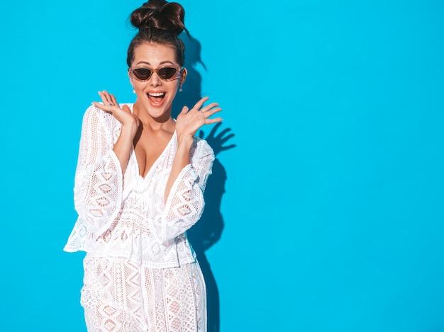 Młoda piękna seksowna uśmiechnięta kobieta z gul fryzurą modna dziewczyna w przypadkowego lata modnisia białym kostiumu odziewa w okularach przeciwsłonecznych. gorący model na niebieskim tle. wstrząśnięty i zaskoczony rękami w pobliżu twarzy