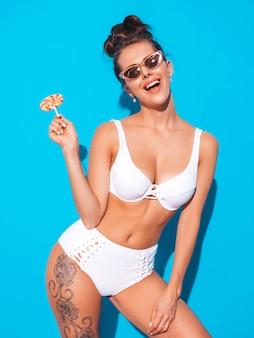 Młoda piękna seksowna uśmiechnięta kobieta z gul fryzurą. modna dziewczyna w swobodnym letnim białym stroju kąpielowym w okularach przeciwsłonecznych. gorący model na niebieskim tle. jedzenie, gryzący cukierek lollipop