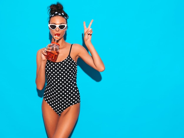 Młoda piękna seksowna uśmiechnięta modniś kobieta w okularach przeciwsłonecznych dziewczyna w letnim groszku stroju kąpielowym kostiumu kąpielowego pozuje blisko błękitnej ściany, pije świeżego koktajlu smoozy napój. pokazuje znak pokoju