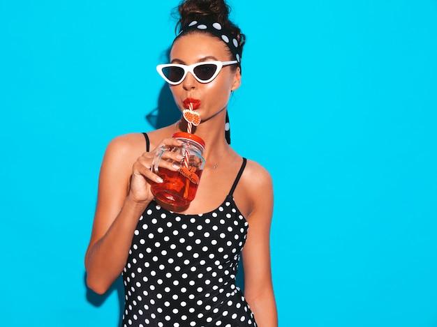 Młoda piękna seksowna uśmiechnięta modniś kobieta w okularach przeciwsłonecznych dziewczyna w letnim groszku stroju kąpielowym stroju kąpielowym pozuje blisko błękitnej ściany, pije świeżego koktajlu smoozy napój
