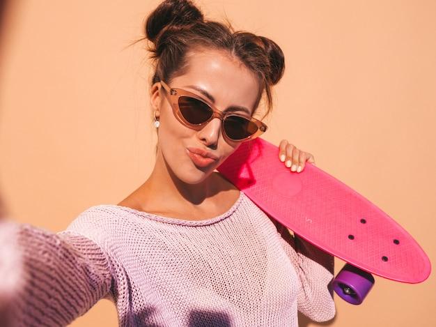 Młoda piękna seksowna uśmiechnięta modniś kobieta w okularach przeciwsłonecznych. modna dziewczyna w lato kardigan z dzianiny. kobieta z deskorolka różowy grosz, na białym tle na beżowej ścianie. wykonywanie autoportretów zdjęcia na telefonie