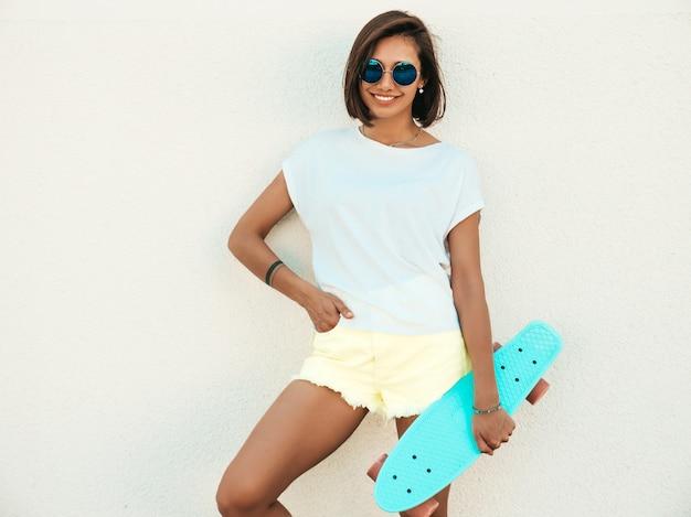 Młoda piękna seksowna uśmiechnięta modniś kobieta w okularach przeciwsłonecznych. modna dziewczyna w lato koszulce i skrótach. pozytywna kobieta z deskorolka błękitny centem pozuje na ulicy blisko białej ściany