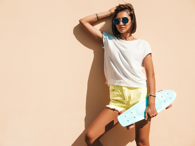 Młoda piękna seksowna uśmiechnięta modniś kobieta w okularach przeciwsłonecznych. modna dziewczyna w lato koszulce i skrótach. pozytywna kobieta z deskorolka błękitny centem pozuje na ulicy blisko ściany