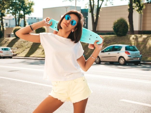 Młoda piękna seksowna uśmiechnięta modniś kobieta w okularach przeciwsłonecznych. modna dziewczyna w lato koszulce i skrótach. pozytywna kobieta z deskorolka błękitny centem pozuje na ulicznym tle
