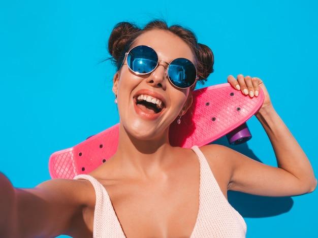 Młoda piękna seksowna uśmiechnięta modniś kobieta w okularach przeciwsłonecznych.