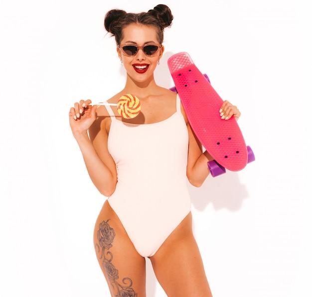 Młoda piękna seksowna uśmiechnięta modniś kobieta z czerwonymi wargami w okularach przeciwsłonecznych. dziewczyna w lato stroju kąpielowego kostiumie kąpielowym.